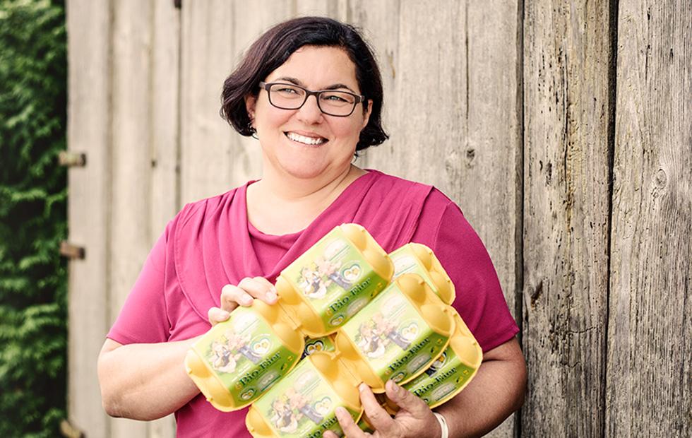 Gerlinde Wagner mit Eierschachteln der Biohennen im Arm.